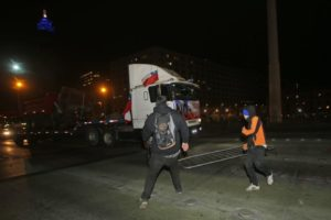 Demonstrators try to stop a caravan of trucks as they drive into Santiago, Chile, Thursday, Aug. 27, 2015. Violent clashes broke out in front of Chile's presidential palace as the truck drivers blocking roads outside Santiago reached the capital to protest against arson attacks by indigenous rights militants. (AP Photo/Luis Hidalgo)